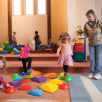 children play in large playroom at Community Child Care Center