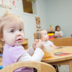 child sits at table at Community Child Care Center