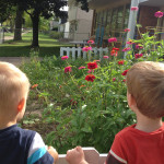 children look at garden flowers at Community Child Care Center