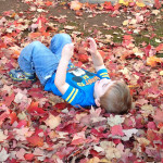 child plays with leaves at Community Child Care Center